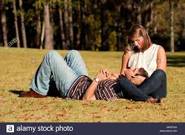 a young couple in love share an intimate moment while laying on a gry field