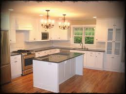 elegant double bronze chandelier over small kitchen island also modish paint cabinets white feat granite countertops