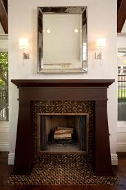the classic dark wood fireplace looks great with a mirror above and two beautiful lights on