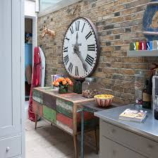 Kitchen clocks  A distressed, colourful sideboard complements this exposed  brick wall. The large clock adds another