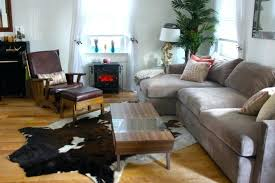 faux cowhide rug plus velvet sectional sofa and brown leather chair with small bench rugs australia
