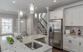small traditional kitchen with white shaker cabinets and stone counter breakfast bar