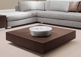 square low profile coffee table painted with brown color on cream carpet tiles for living room with gray sectional sofa with ottoman
