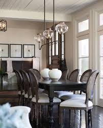 French sunken dining room boasts a plank ceiling accented with a 3 light  linear vintage pendant illuminating a black dining table with turned legs  lined