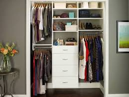 white wooden closet organizer system with 4 drawers and 3 hanger bars