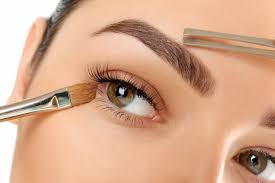 woman contouring eyebrows and applying eye make up jpg