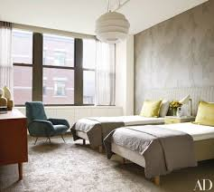in a bedroom at actor will ferrell s manhattan apartment a custom made headboard upholstered in a jim thompson fabric spans the twin beds while the wall
