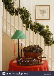 Hall with Christmas garland on staircase above green lamp and decorations on  small table with red cloth