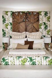 tropical palm themed bedroom with matching bedding wallpaper and a rattan folding screen used as a