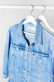 Light Gray Denim Jacket Blue Denim Jacket On White Wooden Coat Hanger On A Rod Against Light Gray Wall Flat Lay Copy Space Denim Fashionable Jacket Womens Or Mens Trend