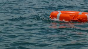 A red rescue buoy floating on the water surface/A first aid training - HD