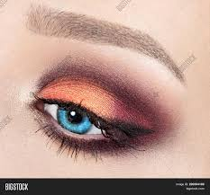 modern fashion makeup closeup on a blue eye bright orange eyeshadow with dramatic cat eye