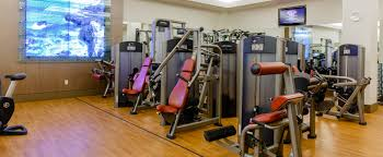 various life fitness resistance machines in a corner area below a wall mounted tv