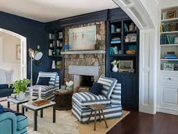 blue cottage den features a wall of navy built in shelves and cabinets flanking a rustic stone fireplace