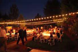 backyard wedding lighting ideas. backyard wedding with italian string lights hung overhead and candles in hundreds of mason jars on lighting ideas