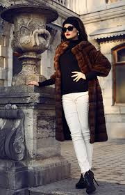 a woman standing in elegant courtyard wears a dark brown fur over a black turtleneck and