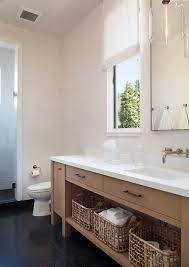 beautiful long bathroom features a long warm brown vanity topped with contrasting white quartz countertop framing sink under wall mounted faucet in satin