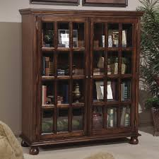 tall and large dark brown wood bookshelf with double glass doors and rack inside also four