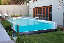 stylish above ground pool with glass enclosure for modern exterior design using white wall color and perfect lawn