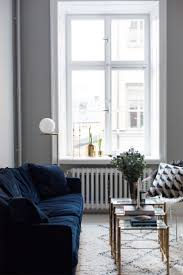 appealing blue velvet sofa with potted plants and glass coffee table plus table lamp also glass window for interior design ideas