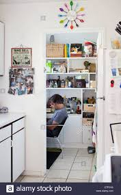 Desk In Kitchen A Man Is Sitting At A Small Desk In A Kitchen Pantry Stock Photo