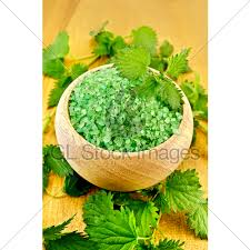 green bath salt in a wooden bowl with nettles o