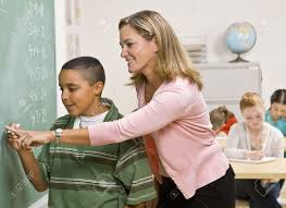 helping math teacher helping child at chalkboard stock photo  teacher helping student at blackboard stock photo picture and stock photo teacher helping student at blackboard