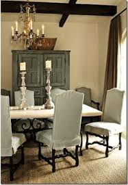 slipcovered dining chairs wrought iron table base seagr rug cream walls dark