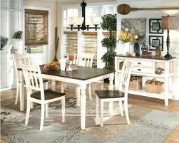 dark wood dining table with white chairs square top and legs of cream wall painting black