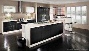 a black and white kitchen by alno with a bi level island and