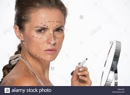 Woman with plastic surgery marks on face holding mirror and marker