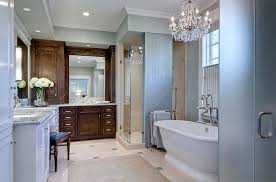 classic glass chandelier shines in the traditional bathroom design domiteaux baggett architects
