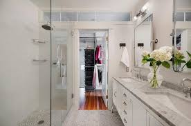 chic walk through master bathroom boasts a restoration hardware pharmacy double vanity topped with carrara marble fitted with white porcelain sinks and