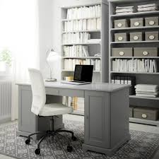 home office table. a home office with grey desk bookcases and swivel chair white cotton table
