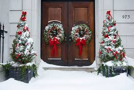 Alberta spruce trees decorated for Christmas and flanking a front door with  wreaths.