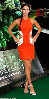 Megan Fox shows off tattoos in orange dress at Teenage Mutant.