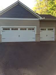 nice white carriage garage doors with a tan home and brick foundation