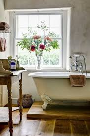 country bathroom colors: clawfoot tub with coiffeuse marble topped table and wood floors nice country bathroom