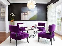 4 piece purple velvet armless accent chairs and round coffee table under modern chandelier in small living room design with black and white wall paint