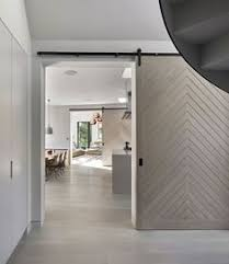 dramatic sliding doors separate. Large Light Grey Wood Barn Doors Have Been Used In This Home To Separate The Various Dramatic Sliding