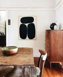 modern rustic dining room design featuring a framed contemporary black and white art print mid century modern chest and a rustic wood table and chairs