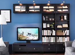 A TV and books stored in an entertainment console with bookshelves to the  right side against