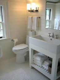 white bathroom features tongue and groove paneled walls framing lacquer mirror over washstand with shelf next to towel rack toilet wall paneling p