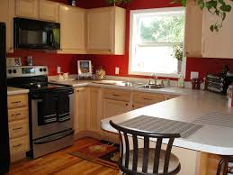 kitchen red wall theme added by cream wooden kitchen cabinet and glass window stunning