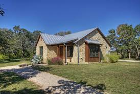 Rustic texas hill country home in small sizes with metal roofing and natural stone wall system