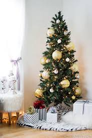 Skinny Christmas tree with large gold ornaments. Great for big impact in a  small space