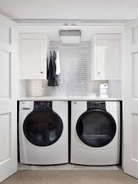 Example of a transitional single-wall laundry closet design in New York  with white cabinets