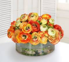 faux mix orange ranunculus in round glass bowl