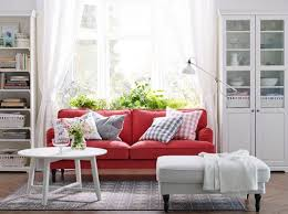 A white living room with a red STOCKSUND sofa, LIATORP cabinet and bookcase  in white