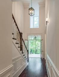 2 story foyer chandelier hallway wainscoting two carriage lantern transom window simple height